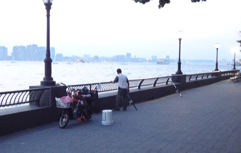 Fisherman on esplanade by West Thames